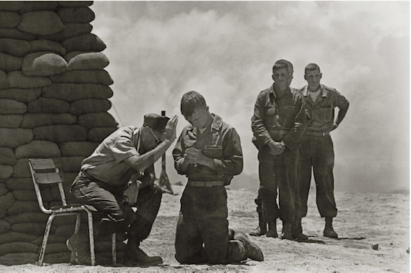 On a hill in Da Nang, Vietnam, a priest hears soldiers' confessions, 1969