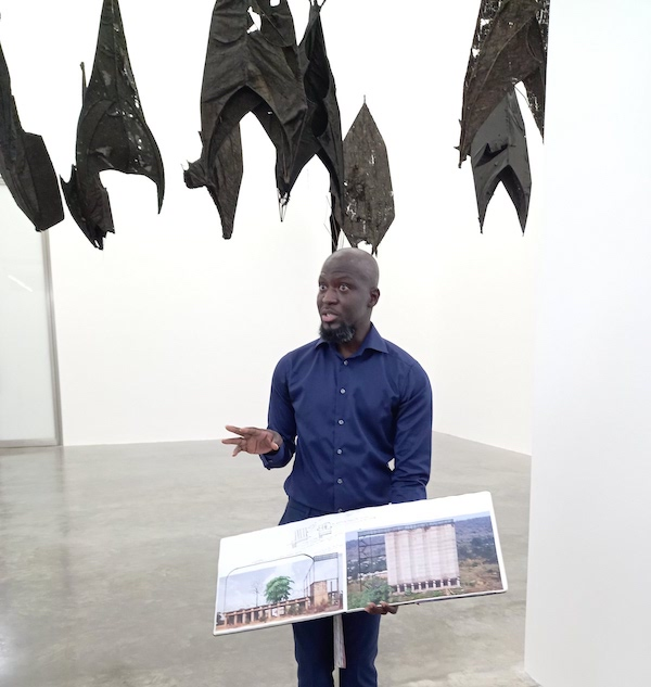 Ibrahim Mahama explains his process using his notebooks with images of silos, in front of 'Lazarus', 2021